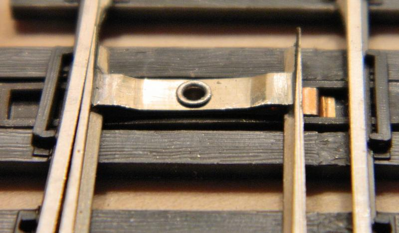 shinohara's idea of a locking spring - a brass piece under the connecting  bar that is supposed to latch under the foot of the rail